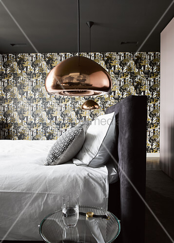 Copper-coloured ceiling lamps above bed in front of patterned wallpaper