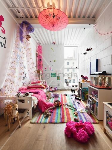 kinderzimmer mit buntem teppich baldachin bett und auf dem boden spielendem m dchen bild. Black Bedroom Furniture Sets. Home Design Ideas