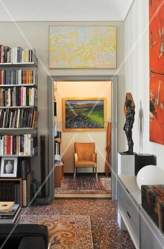 Eleganter Wohnbereich mit Bücherregal, Terrazzoboden und Blick auf Armlehnstuhl