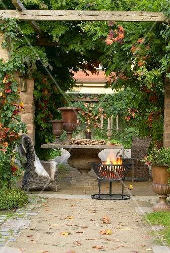 Herbstlicher Sitzplatz mit berankter Pergola und Feuerkorb