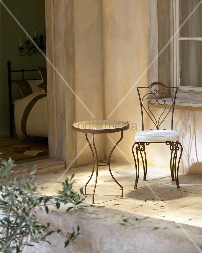Verschnörkelter Metallstuhl und ein runder Tisch auf der Terrasse
