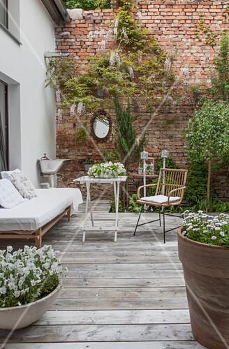 Gemütliche Terrasse vor dem Haus und einer Backsteinmauer