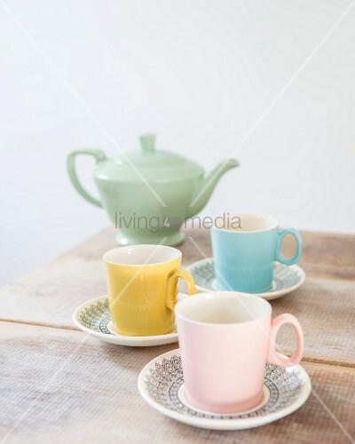 Pastellfarbenes Retro Teegeschirr auf rustikalem Holztisch