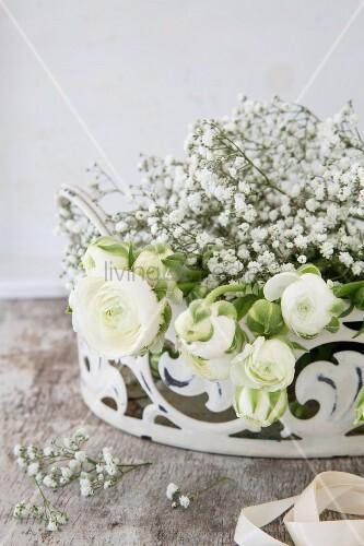 White ranunculus and gypsophila in white metal basket