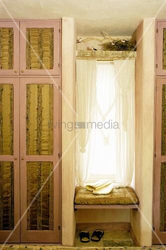 Narrow window seat between fitted wardrobes in bedroom