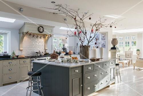 helle offene k che im landhausstil mit dekozweigen auf der insel bild kaufen living4media. Black Bedroom Furniture Sets. Home Design Ideas