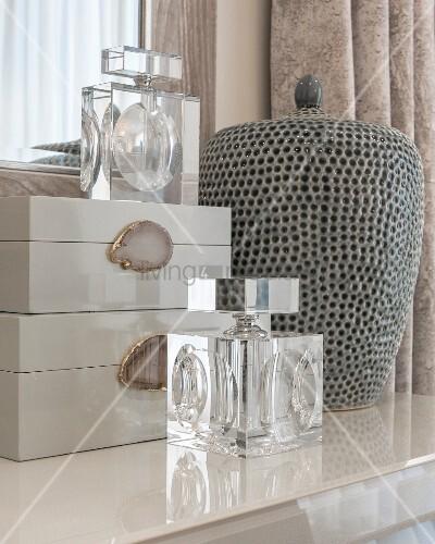 Elegant perfume bottles and boxes next to ceramic vase