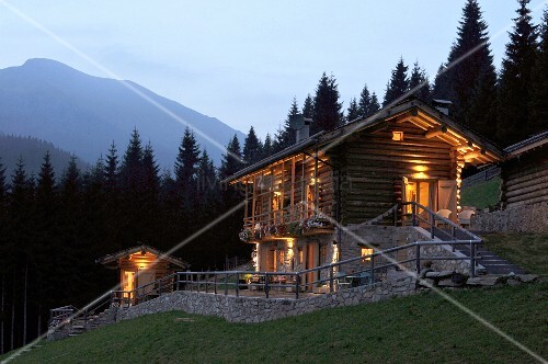 Log cabin with illuminated windows in mountains