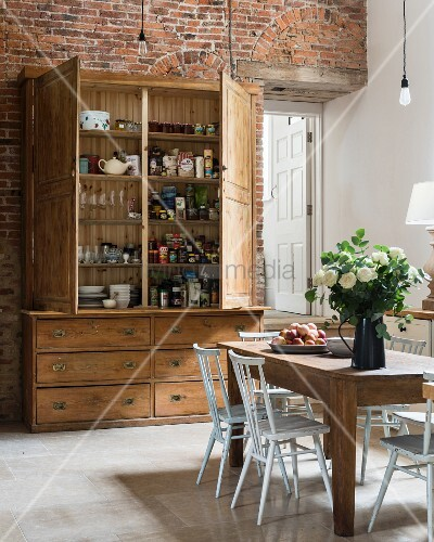 Rustic wooden cupboard with open doors and dining table in spacious kitchen with exposed brick wall