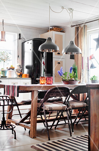 Folding metal chairs around wooden table in country-house kitchen