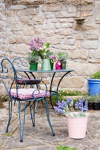 Dekorierter Sitzplatz auf der Terrasse vor einer Natursteinwand