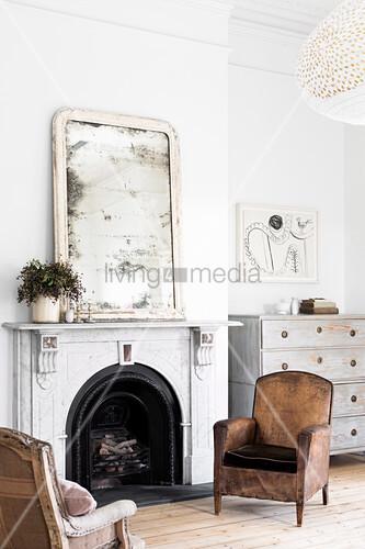 Zwei alte Sessel vor offenem Kamin mit blindem Spiegel auf der Konsole