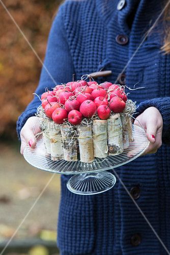 Cake-shaped arrangements of natural materials held in hands