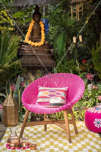 Pink wicker armchair and colourful decorations on rug in garden