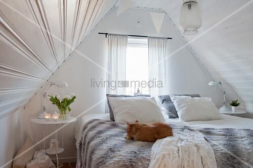 Gemütliches Schlafzimmer in Weiß unter dem Giebel