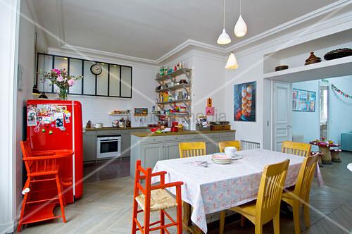 Offene Küche in Altbauwohnung mit bunten Möbeln und Esstisch