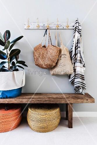 Alte Garderobe über einer schlichten Holzbank mit Körben