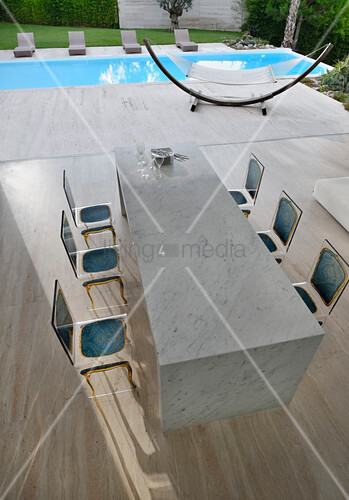 Marble table and acrylic Baroque-effect chairs in front of pool