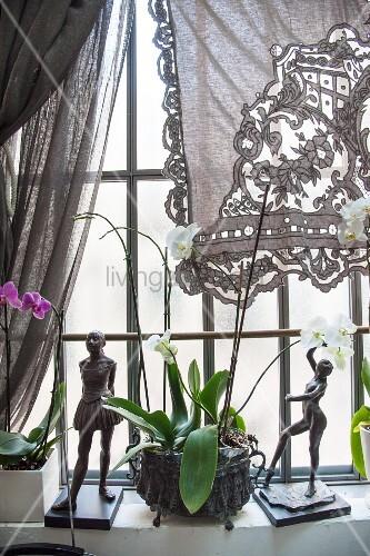 Spitzenvorhang und zwei Skulpturen mit Orchideen auf Fenstersims