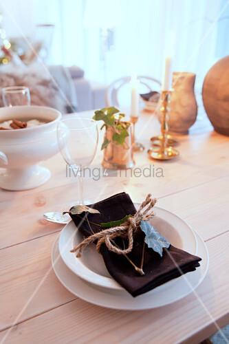 Schleife aus grober Schnur um Serviette und Efeuranke auf dem Teller