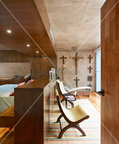 Bed behind partition wall and collection of crucifixes in bedroom