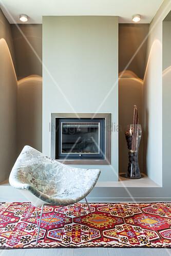 Designersessel auf gemustertem Teppich vor Kamin