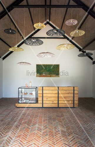 Cubist display case on wooden counter below pendant lamps with parasol lampshades