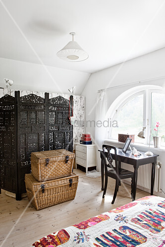 Desk in front of arched window and ornate screen in bedroom