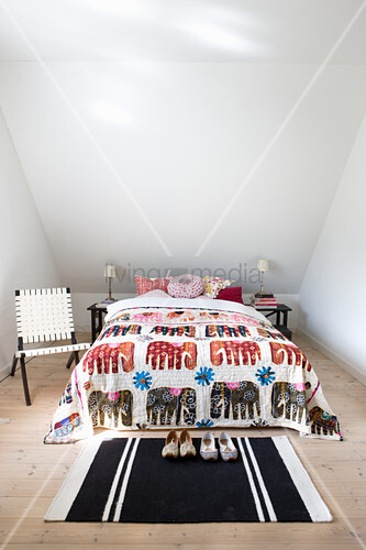 Elephant-patterned bedspread on bed under sloping ceilling
