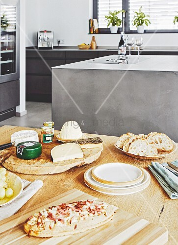 Pizza and a cheese platter on a wooden table with an anthracite-look island in the background
