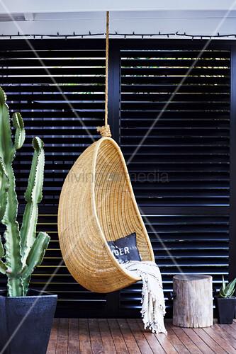 Hängesessel aus Korb vor einer schwarzen Lamellenwand