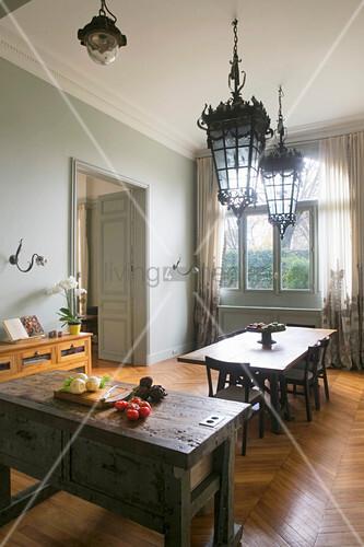 Blick über die Kücheninsel ins Esszimmer mit alten Laternen