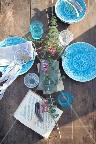 Mit Blauen Tellern gedeckter Holztisch im Sonnenlicht