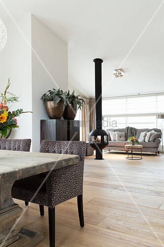Rustic wooden table with elegant upholstered chairs in front of free-standing fireplace in lounge area