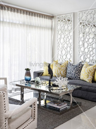 Scatter cushions on sofa in front of large mirrors on wall, mirrored coffee table and armchairs in living room