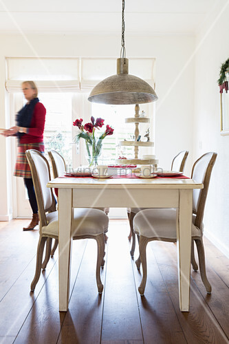 Woman walking behind white dining table with Baroque chairs