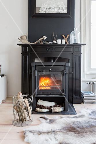 Cast iron log burner in black fire surround against black chimney breast