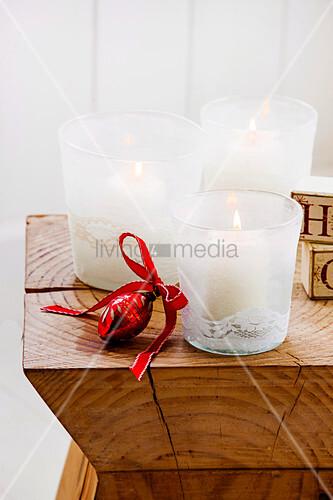 Drei weiße Windlichter mit Spitzenborte auf einem Holzhocker