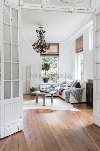 View through old double doors into living room with wooden floor