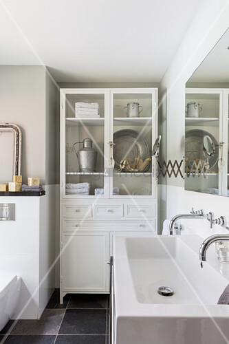 Alter Vitrinenschrank im weißen Bad mit Doppelwaschbecken