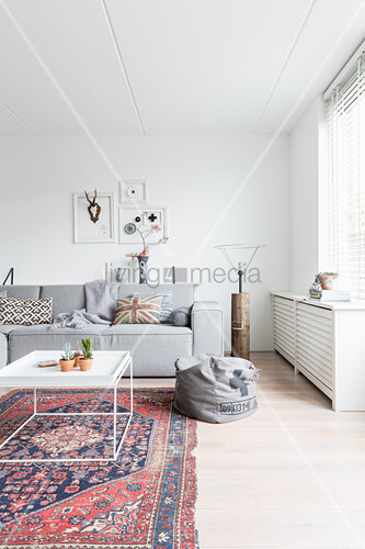 Old rug and modern grey sofa in white living room