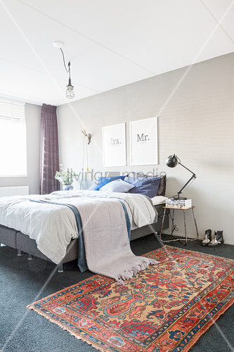 Oriental rug next to bed in bedroom with grey wall
