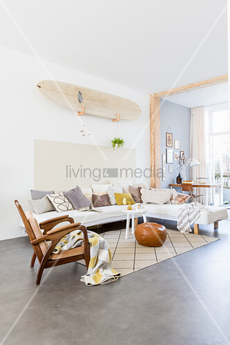 Surfboard on wall above sofa with various scatter cushions