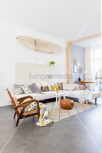 Surfbrett an der Wand über dem Sofa mit verschiedenen Kissen