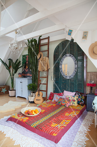 Colourful bed in attic bedroom with Mexican ambiance