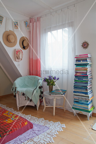 Ombré curtains and colourful stack of books next to window