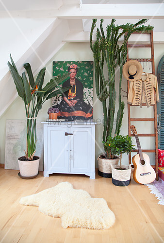 House plants around picture of Frida Kahlo on top of small cabinet