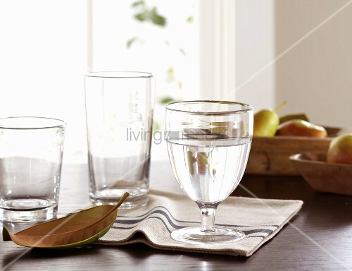Glasses of water, striped napkins and fruit on table