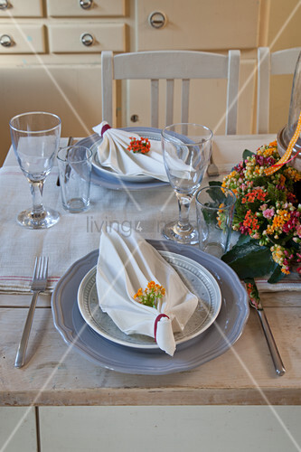 Set table decorated with folded serviettes and flower arrangement