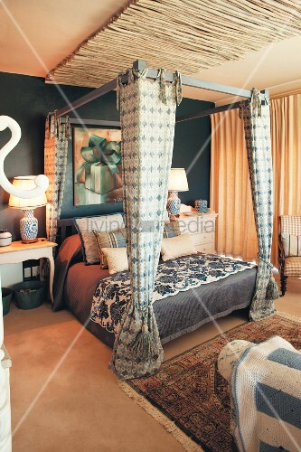 Four-poster bed and petrol-blue wall in bedroom